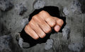 Fist breaking old dirty concrete wall Royalty Free Stock Photo