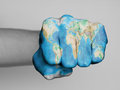 Fist of a man punching very hairy knuckles from the world map print Royalty Free Stock Images