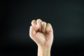 Fist up male s hand with clenched on black background Stock Photography
