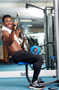 Fit african trainer working out in multi gym Stock Photo