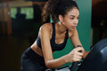 Fit afro american woman exercising on spinning bike at cardio class at gym Royalty Free Stock Photo
