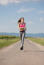 Fit and agile young brunette woman running outdoors in the sunshine Royalty Free Stock Images