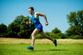 Fit athlete running hard on a sunny day young practicing increasing his stamina Royalty Free Stock Images
