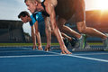 Fit athlete running race in athletics racetrack on a sunny day two young athletes at starting position ready to start sprinters Royalty Free Stock Image