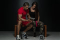 Fit attractive young couple looking at a tablet digital table in studio on black background Royalty Free Stock Photography