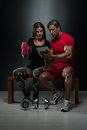 Fit attractive young couple looking at a tablet digital table in studio on black background Royalty Free Stock Images