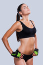 Fit and beautiful young sporty woman with perfect body holding hands on hip keeping eyes closed while standing against grey Stock Photography
