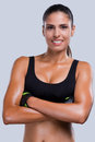 Fit and beautiful young sporty woman in sports clothing keeping arms crossed smiling while standing against grey background Stock Image