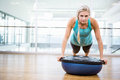 Fit blonde doing push up on bosu ball Royalty Free Stock Photo