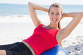 Fit blonde doing sit ups on exercise ball the beach Royalty Free Stock Images