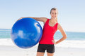 Fit blonde holding exercise ball smiling at camera on the beach Royalty Free Stock Image