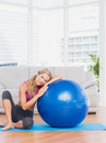 Fit blonde sitting beside exercise ball smiling at camera home in the living room Royalty Free Stock Photos