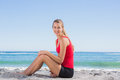 Fit blonde sitting on sand smiling at camera the beach Stock Photography