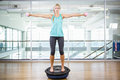 Fit blonde standing on bosu ball and lifting dumbbells Royalty Free Stock Photo