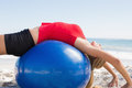 Fit blonde stretching back on exercise ball the beach Royalty Free Stock Images