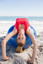 Fit blonde stretching back on exercise ball smiling at camera the beach Stock Photo