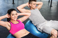Fit couple doing abdominal crunches on fitness ball at crossfit gym Stock Photography