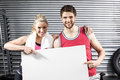 Fit couple holding blank paper at crossfit gym Stock Photography