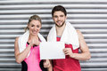 Fit couple holding blank paper at crossfit gym Royalty Free Stock Image