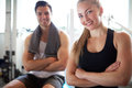 Fit couple smiling at camera with arms crossed close up young after workout inside the gym in front their bodies Royalty Free Stock Image