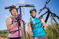 Fit couple walking down trail smiling at camera holding mountain bikes Royalty Free Stock Photo