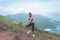 Fit female jogger exercising, running uphill with sea and mountains in background Royalty Free Stock Photo