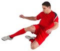 Fit football player jumping and kicking on white background Stock Photos