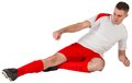 Fit football player playing and kicking on white background Stock Images