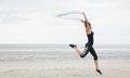 Fit girl leaping with scarf at the beach Royalty Free Stock Photo