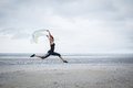 Fit girl leaping with scarf at the beach Stock Photos