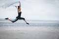 Fit girl leaping with scarf at the beach Royalty Free Stock Images