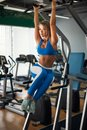 Fit girl training abs by raising legs on a horisontal bar.