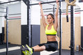 Fit girl training abs by raising legs on a horisontal bar. Fitness woman workout doing exercises at gym. Royalty Free Stock Photo