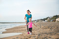 Fit, happy mother running behind young daughter on the beach Royalty Free Stock Photo