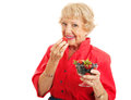 Fit healthy senior lady eating berries woman biting into a strawberry and holding a bowl of mixed Stock Images