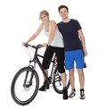 Fit healthy young couple who enjoy an active outdoor lifestyle standing with bicycle Royalty Free Stock Photography
