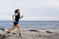 Fit and healthy young woman running along shoreline caucasian female athlete exercising on beach beautiful Royalty Free Stock Images