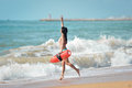 Fit lady in bikini with life-saver running into Royalty Free Stock Photo
