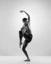 A fit male dancer posing on a grey background young handsome sporty and athletic ballet dance black and white image Royalty Free Stock Photos