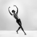 A fit male dancer posing on a grey background young handsome sporty and athletic ballet dance black and white image Royalty Free Stock Images