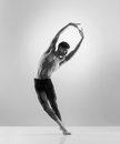 A fit male dancer posing on a grey background young handsome sporty and athletic ballet dance black and white image Royalty Free Stock Photography