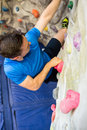 Fit man rock climbing indoors Royalty Free Stock Photo