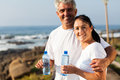 Fit mature couple drinking water at the beach after exercise Royalty Free Stock Images