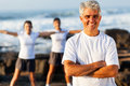 Fit mature man men on beach with family exercising on background Royalty Free Stock Images