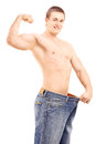 Fit muscular man in a big pair of jeans showing his biceps isolated on white background Royalty Free Stock Images