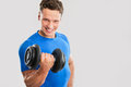 Fit muscular man exercising with dumbbell on gray background Stock Photo