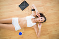 Fit smiling woman doing sit ups at home on parquet floor Royalty Free Stock Image