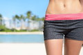 Fit sporty woman hips lower body female closeup young adult wearing sexy sports shorts for fitness exercise or running with beach Stock Photography