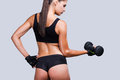 Fit and toned rear view of young sporty woman with perfect buttocks exercising with dumbbells while standing against grey Stock Photos
