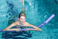 Fit woman doing aqua aerobics with foam rollers Royalty Free Stock Photo